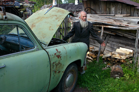 gaffer: Leningrad area of St. Petersburg, Russia - August 23, 2006: Valentin Stepanovich Shramko born in 1938, Elderly gray-bearded peasant farmer standing near a light green old car, Russian, Soviet-made brand Moskvich 403.
