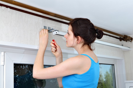 fastens: Girl installs vertical blinds, fastens to the wall mount.