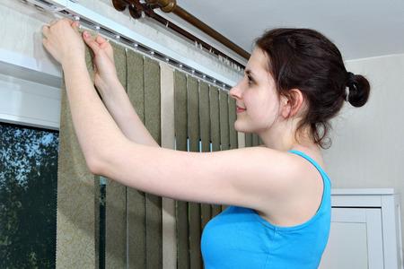 Install blinds. Girl hanging blinds, vertical blind fabric slats hook onto rail.  版權商用圖片