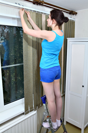 snapped: Girl attach slats, vertical fabric blinds to rail Stock Photo