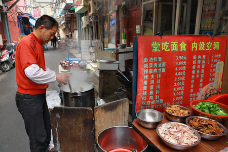 concoct: Shanghai, China - April 20, 2010: Outdoor eatery in the open, the chef prepares food on the street.