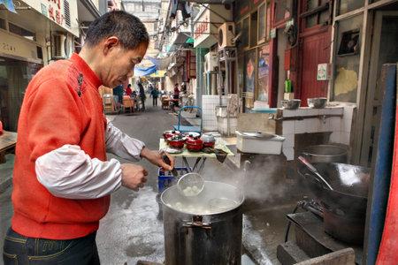 concoct: Shanghai, China - April 20, 2010: Seller street food, outdoor, cooking dumplings in a big pot Editorial