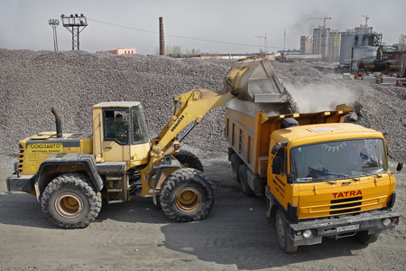 St. Petersburg, Russia - April 27, 2009: Construction equipment and machinery, a pile of construction gravel, yellow digger loads crushed stone into orange dumper truck tipper.