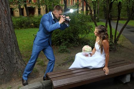 honeymooners: Sesi�n de fotos de boda, un novio con una c�mara en mano, fotografiando la novia. Foto de archivo