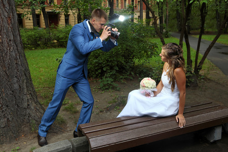 honeymooners: Wedding photo session, a bridegroom with a camera in hand, photographing the bride.