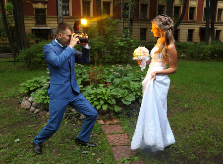 female photographer: Professional wedding photographer takes a picture of the bride, camera flash flashing