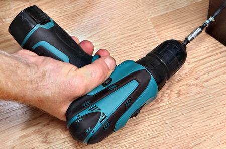 Hand holding a cordless screwdriver, screwing Chipboard screws, closeup. photo