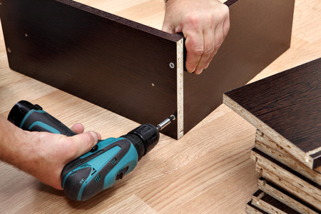 Montaje de muebles de aglomerado, con un destornillador inalámbrico, de cerca.