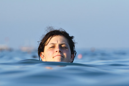 Head of one caucasian young girl bathing in sea water, is visible above the water, on the background of the vast, empty sea
