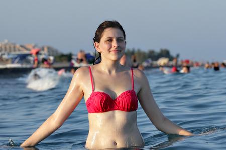 bathers: Una giovane donna caucasica, 19 anni, cintura in piedi profondo in acqua sulla spiaggia di sfondo con un sacco di bagnanti e di prendere il sole e turisti. Archivio Fotografico