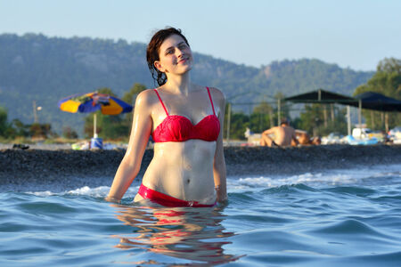 Young woman standing in the deep sea water on the background of the beach and wooded hills in Turkey near the town of Kemer Antalya Province in the summer in the evening. photo