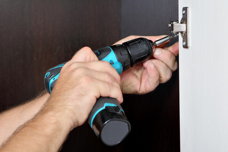 Carpenter mounts wardrobe, screwing a screw, furniture door hinge, using cordless screwdriver. photo