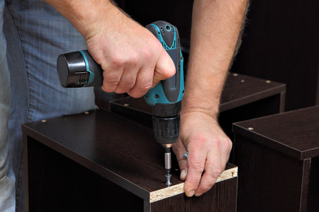 tool cabinet: Assembling furniture, Hands of a carpenter with a electric Cordless screwdriver, tighten the screw in drawers of chipboard.