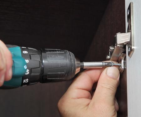 closet door: Furniture assembly, joiner mounts door hinges closet for clothes using cordless screwdriver. Stock Photo
