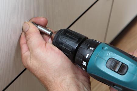 keyless: Assembling furniture, close-up photo, sleeve keyless chuck cordless screwdriver screw is screwed Stock Photo