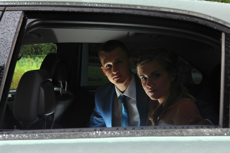 Young couple in car salon, newlyweds look out the window photo