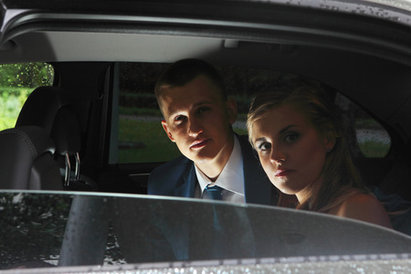 Newlyweds look out the window cars wedding car, while the rear seat photo