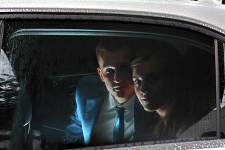 drop in: Two newlyweds sitting in the car, in the passenger seat and look out the window with raindrops on glass.