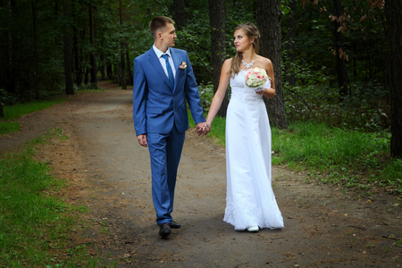 newly married: Newly married couple walk on park paths holding hands and looking at each other. Stock Photo