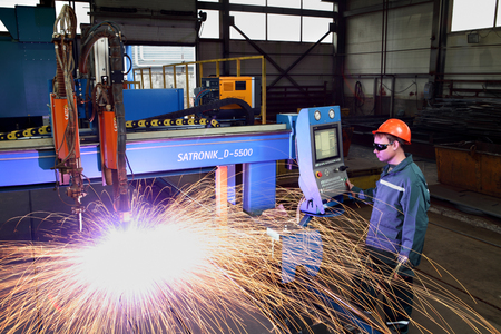 Saint-Petersburg, Russia - October 10, 2014: Factory production of metal, worker working in a helmet and goggles, controls the plasma metal cutting, standing next to the display remote control of the machine sparks fly.