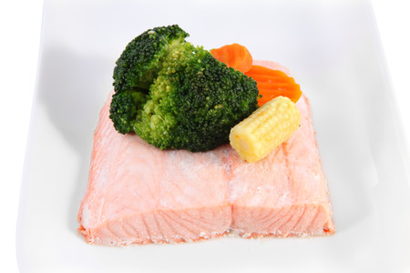Closeup of salmon fillets steamed on a plate with vegetables, marinated young cob corn, and broccoli. photo