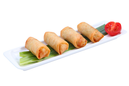 Four fried Chinese spring rolls in a row on a white, long, narrow porcelain plate, decorated with a stalk of green onion and half a tomato, isolated on white background. photo