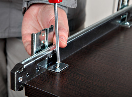 Realign a wood furniture metal-drawer track, Mounting furniture slide rail track  computer desk keyboard tray. Stock Photo