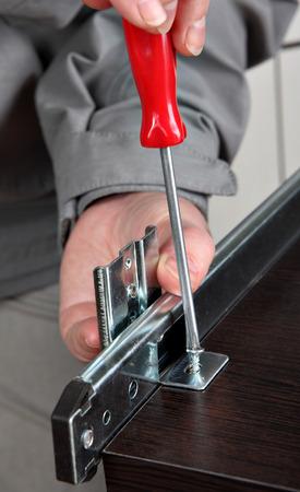 Assembling furniture, Installing Cabinet Drawer Runners, drawer slide rear mounting bracket, screwing screw manual screwdriver.
