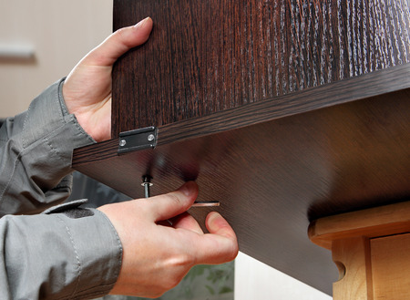 adjusting screw: Assembling of furniture with a hexagon furniture key in hand of the master. Hand holds allen key furniture inserted into the bolt head. Allen furniture key in hand, fastens screw, close-up. Carpenter holds chipboard furniture wenge color is dark brown.