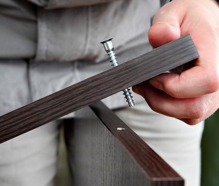 furniture hardware: Instalaci�n y montaje de los muebles, el uso de elementos de fijaci�n, tornillo de madera para atornillar la conexi�n de dos tableros de aglomerado, de color wengu� de color marr�n oscuro, primer plano. Foto de archivo