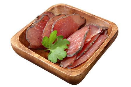 piggish: Jamon cured pork meat sliced on wooden bowl,  isolated on white background.