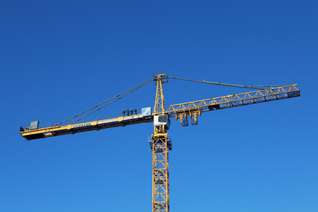 St. Petersburg, Russia - October 30, 2014: Crane erection process, tower crane assembly.  Installers high altitude ,  stands on counterweight jib yellow tower crane.