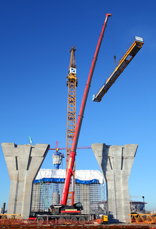 jib: St. Petersburg, Russia - October 29, 2014:  The Counter Jib Is Installed. Red mobile crane lifts a section of yellow tower crane on a background of blue sky in sunny weather, installation, assembly of the crane.