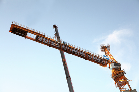 an erection: St. Petersburg, Russia - October 29, 2014:  The erection of a tower crane. Section of tower crane assembly, mounting counterjib to the tower mast. Editorial