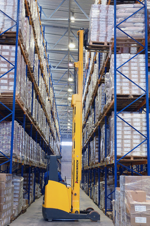 St. Petersburg, Russia - November 21, 2008: Yellow pedestrian stacker lifts pallet with boxes on the shelves. Forklift pallet truck lifts the pallet in the narrow aisle warehouse. Yellow fork lift truck with raised fork.