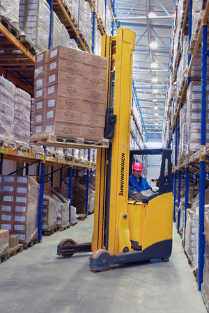 St. Petersburg, Russia - November 21, 2008: Yellow Forklift pallet truck lifts the pallet in the narrow aisle warehouse. Forklift raises palletising on top shelf of the rack.