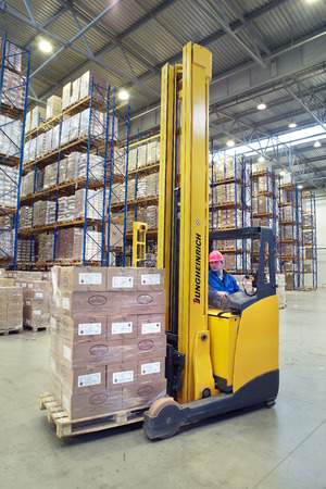 inventories: St. Petersburg, Russia - November 21, 2008: The driver of a yellow forklift truck operates, in warehouses, sitting in the workplace. A fork lift truck moves stacked pallets. Forklift palletiser carrying palletising on the territory of the warehouse with p