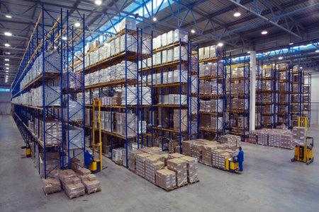 San Petersburgo, Rusia - el 21 de noviembre de 2008: paletizador Forklift llevar paletización en el territorio del almacén con sistema de rack de almacenamiento de palets. El interior de un almacén de productos grandes con estanterías de almacenamiento del sistema de plataforma de bastidores.