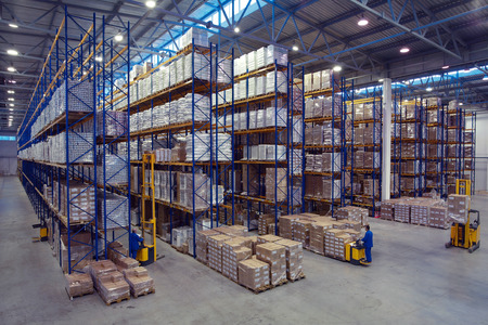 inventories: St. Petersburg, Russia - November 21, 2008: Forklift palletiser carrying palletising on the territory of the warehouse with pallet storage rack system. The interior of a large goods warehouse with shelves of pallet rack system storage.