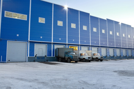 St. Petersburg, Russia - November 21, 2008: Big blue warehouse outside the trucks are unloaded at the loading docks, the evening.