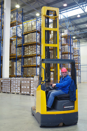 St. Petersburg, Russia - November 21, 2008: The driver of a yellow forklift truck operates, in warehouses, sitting in the workplace.