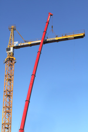 jib: St. Petersburg, Russia - October 29, 2014: Installation work, assembly tower crane on blue sky background. Fixing counter jib to the tower. Yellow construction crane in the assembly process.