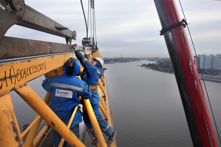 jib: St. Petersburg, Russia - October 30, 2014: Steeplejacking works on installation working console tower crane. The Working Jib of  crane is installed at the turntable and elevated with the Mobile Crane.