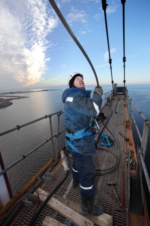 erector: St. Petersburg, Russia - October 30, 2014: Steeplejacking Erector is working at height when installing console section of the tower crane. High-altitude installation work working console tower crane.