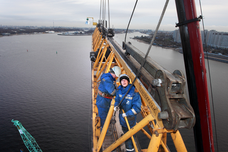 erector: St. Petersburg, Russia - October 30, 2014: The Working Jib of the crane is installed at the turntable and elevated with the Mobile Crane. High-altitude installation work working console tower crane.