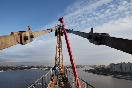 jib: St. Petersburg, Russia - October 30, 2014: Build tower crane, high-altitude mounting works,  Pulling pendant cables up to stabilize jib assembly,  jib tie bars, rear pendant tower crane,  tower peak.
