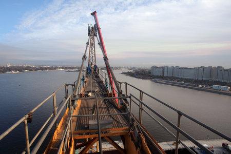 jib: St. Petersburg, Russia - October 30, 2014: Setting tower crane, high-altitude erection works, tower peak, apex, jib tie bars. Making pendant line connections