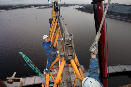 jib: St. Petersburg, Russia - October 30, 2014:    Engineering facility, construction equipment and machinery, installation section of the tower crane at a height, assembly fitters steeplejacks.