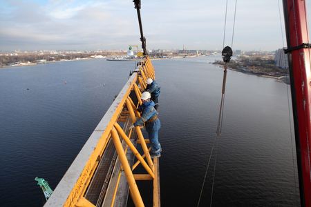 steeplejack: St. Petersburg, Russia - October 30, 2014:    Installers working at high altitude, erecting tower crane lifting construction, industrial photography.