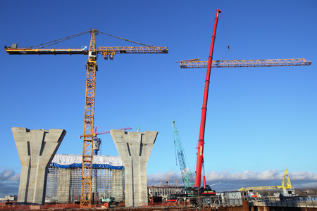 jib: St. Petersburg, Russia - October 30, 2014: Construction plant,  Erection of the towers crane, connecting outer jib to inner jib. Mobile crane lifts up a section of the tower crane, installation works.